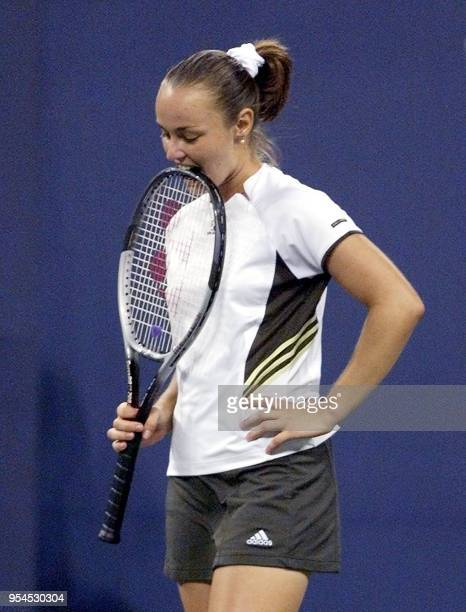 Number one seed Martina Hingis of Switzerland bites her racquet after losing a point to Kvet Hrdlickova of the Czech Reupblic during their first...