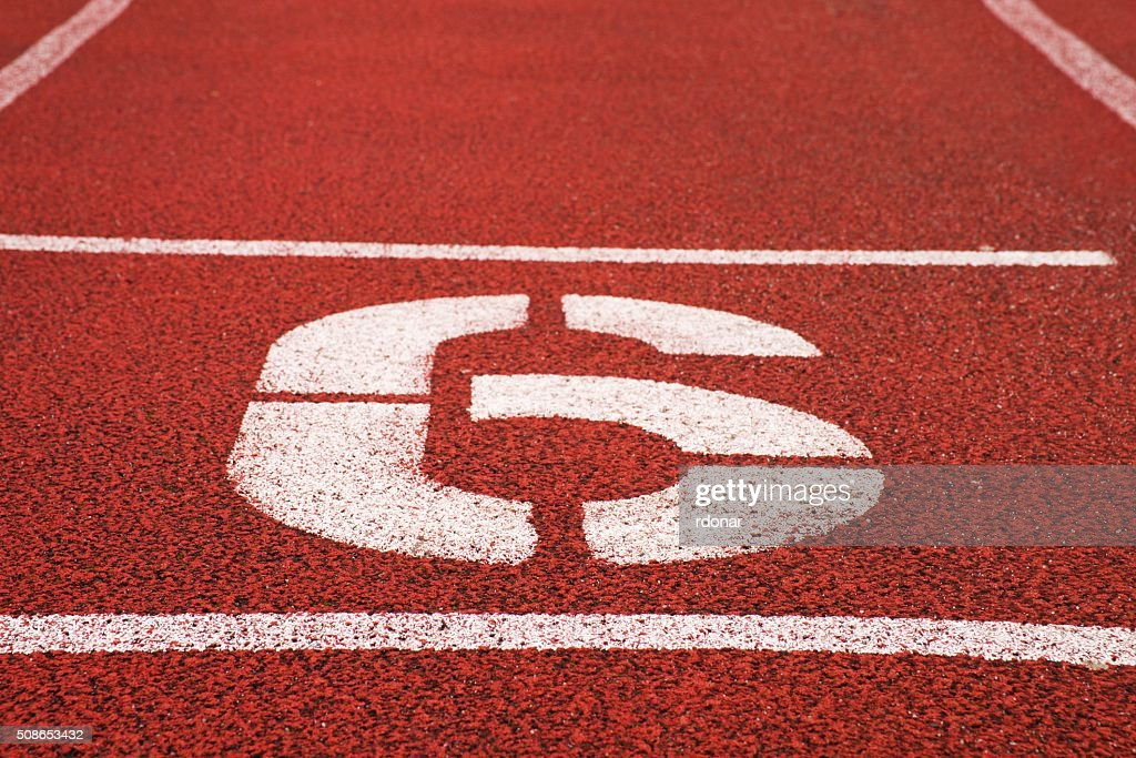 Number six. White athletic track number on red rubber racetrack : Stock Photo