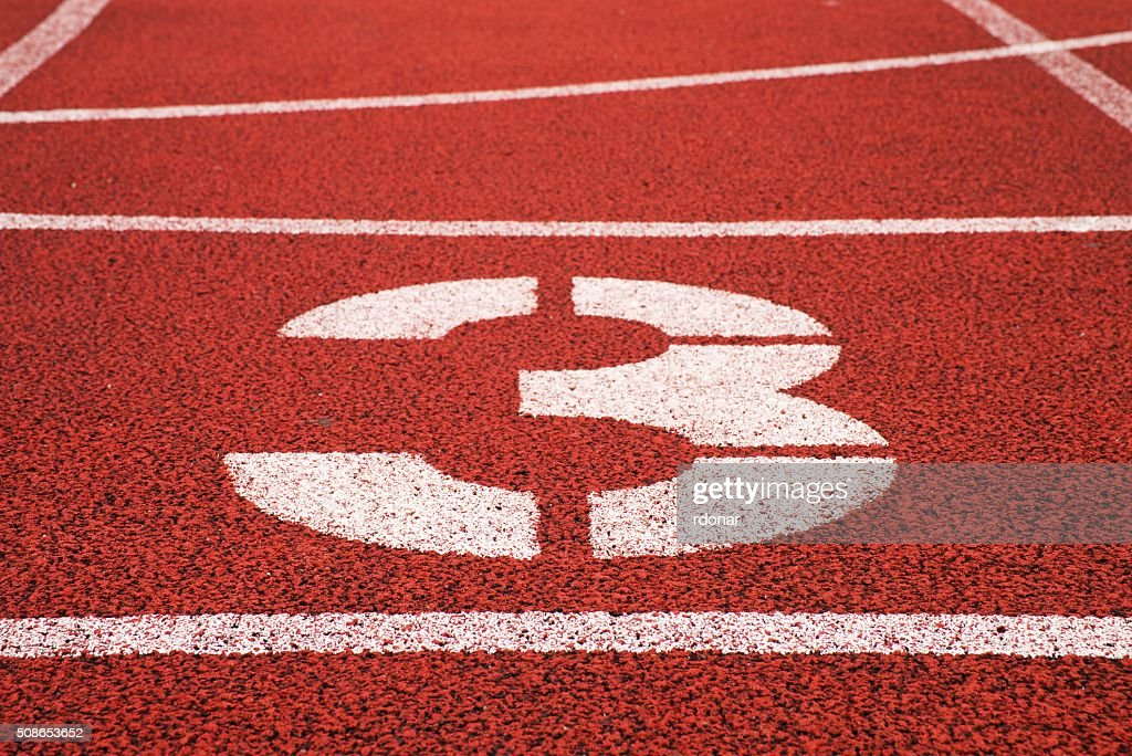 Number three. White track number on red rubber racetrack : Stock Photo