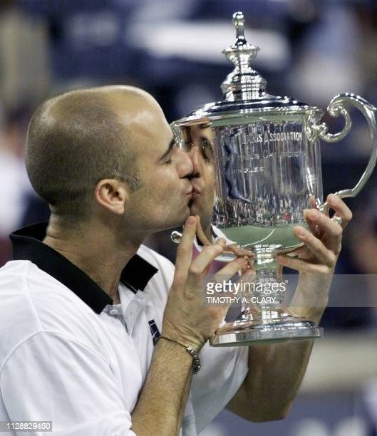 Number two seeded Andre Agassi of the US kisses the US Open trophy after his victory over compatriot and number seven seeded Todd Martin 12 September...