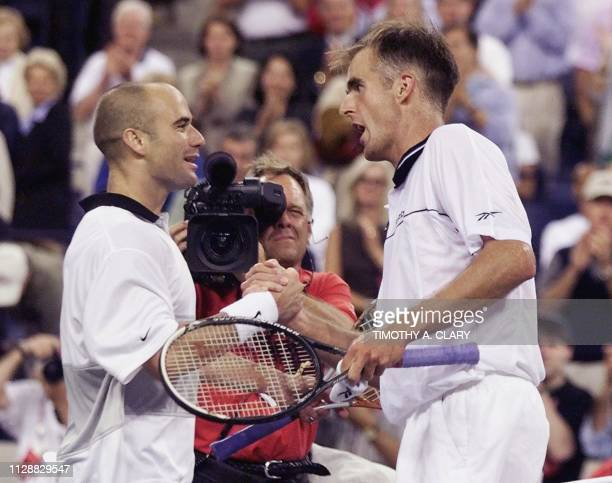 Number two seeded Andre Agassi of the US shakes hands with compatriot and number seven seeded Todd Martin 12 September 1999 at the US Open Men's...