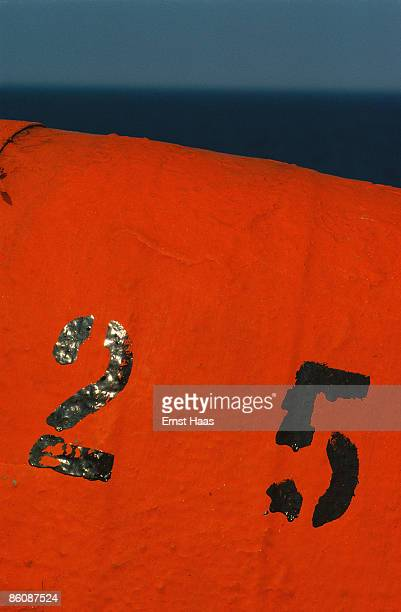 Numbers stencilled in black paint on an orange background July 1972