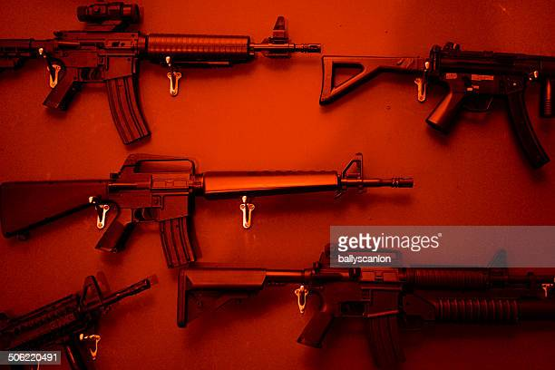 numerous assault rifles hanging on wall. - 銃 ストックフォトと画像