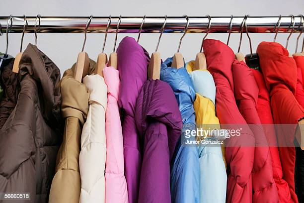 numerous colorful jackets on a rack - coat fotografías e imágenes de stock