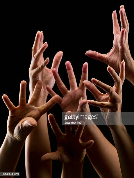 Numerous Female Hands Reaching Out from a Black Background