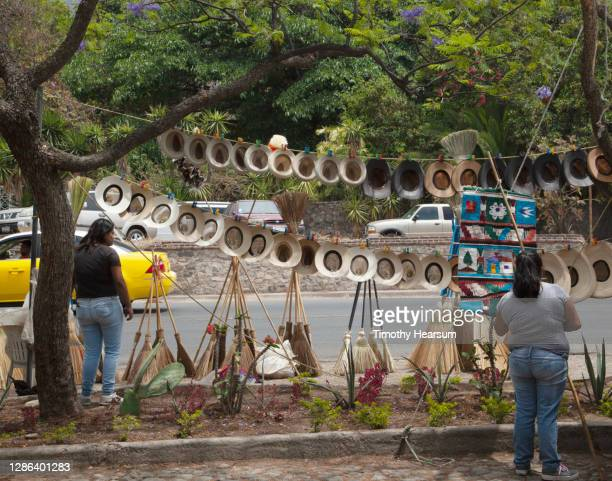 numerous hats, brooms and other items displayed at a street-side market - timothy hearsum stock pictures, royalty-free photos & images