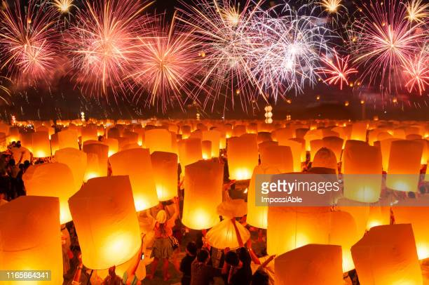 numerous paper lanterns prepared for floating in the sky with fireworks in the background - laisser partir photos et images de collection