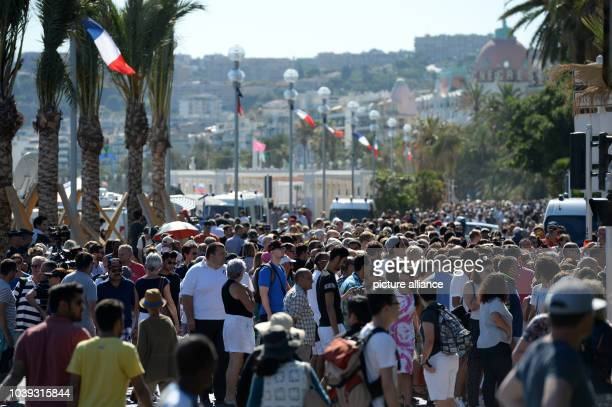 Numerous people flock the Promenade des Anglais at the scene in Nice France July 16 2016 where a truck drove into a crowd during Bastille Day...