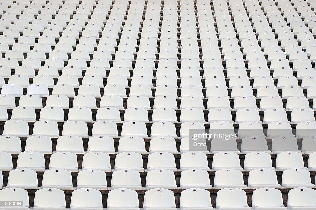 Numerous rows of white stadium seats : Stock Photo