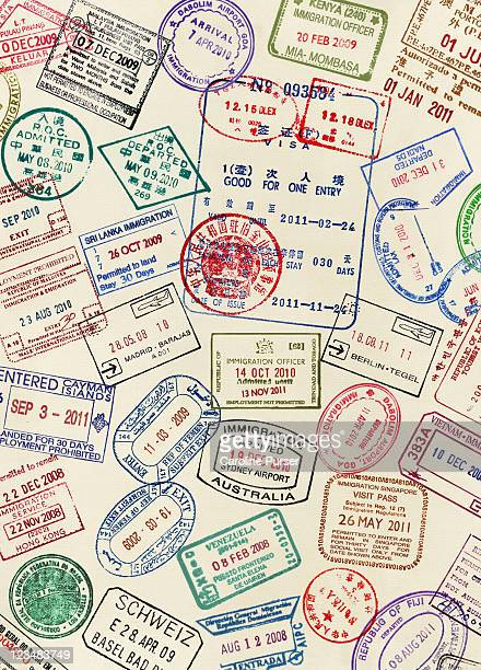 numerous visa stamps on a passport page - passeport photos et images de collection