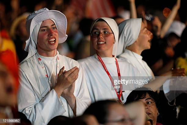 A nun and a pilgrim attend a prayer vigil led by Pope Benedict XVI on a vast dusty esplanade outside Madrid during the World Youth Day festivities on...