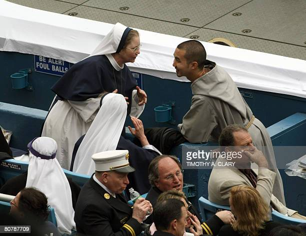 A nun and monk talk behind 3rd base while waiting for the mass of Pope Benedict XVI to begin at Yankee Stadium April 20 2008 in New York City The...