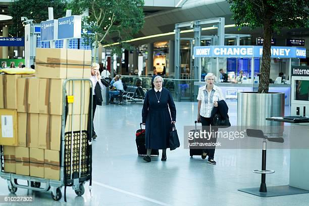 Nun and senior woman at airport
