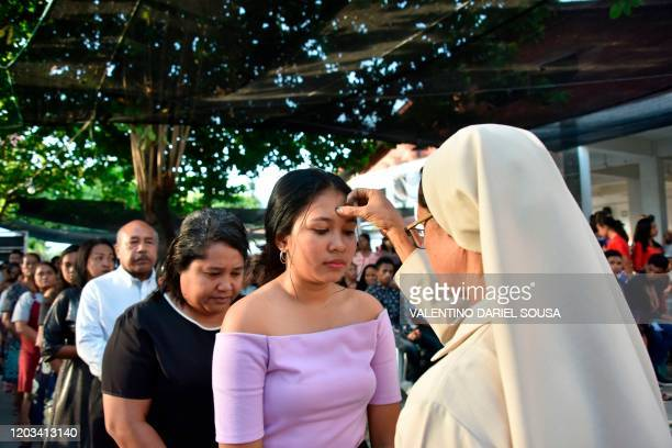 A nun applies ash to a woman's forehead during Ash Wednesday at the Motael church in Dili on February 26 2020 The 40day period of Lent begins on Ash...