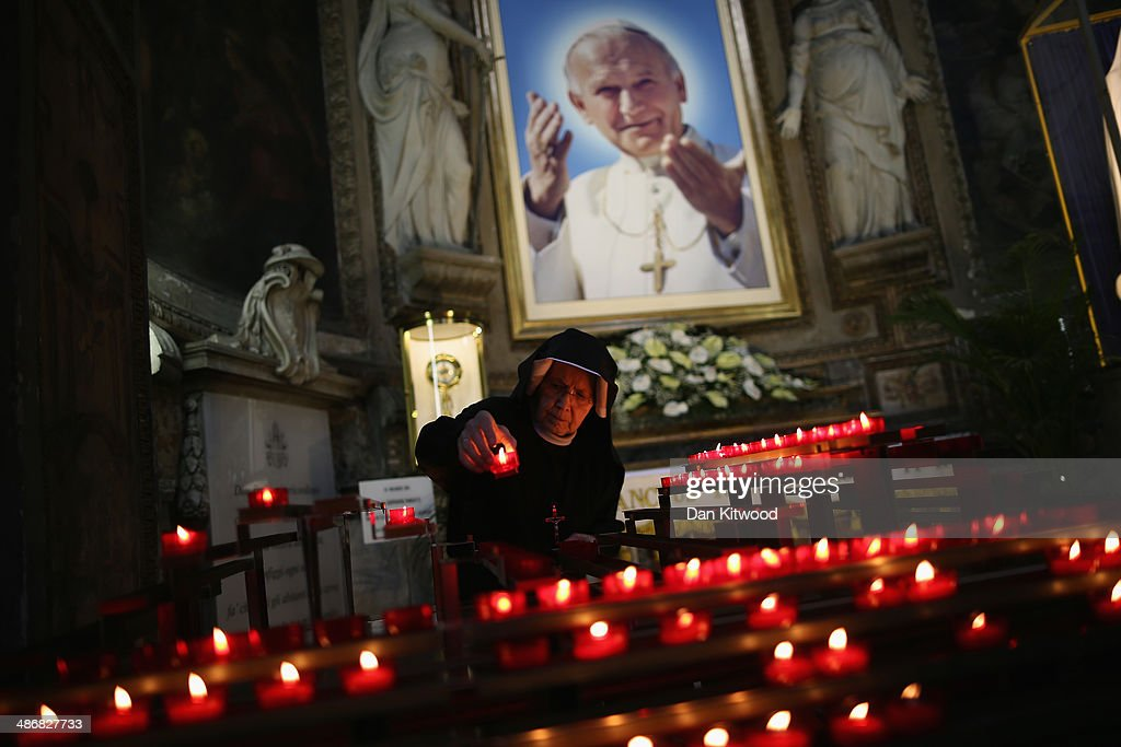 A nun arranges candles underneath an image of the late Pope John Paul II at the Polish Church, Santo Spirito in Sassia, Sanctuary of Divine Mercy on April 26, 2014 in Vatican City, Vatican. Dignitaries, heads of state and Royals from Europe and across the World are gathering in the Vatican ahead of tomorrow's canonisations. The late Pope John Paul II and Pope John XXIII will be canonised on Sunday April 27, inside the Vatican when 800,000 pilgrims from around the world are expected to attend.