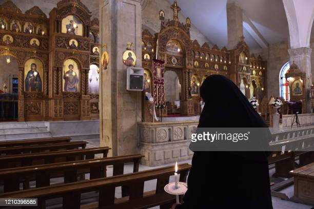 A nun attends a crowdless Easter Sunday mass during a nationwide lockdown to stem the spread of the novel coronavirus at the Prophet Elias Greek...