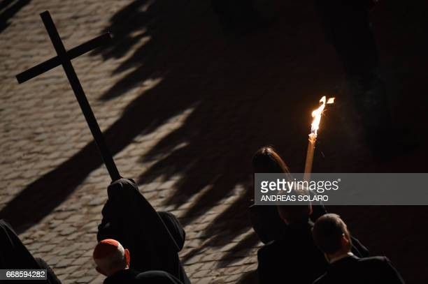 A nun carries a cross during the Via Crucis torchlight procession presided by Pope Francis on Good Friday on April 14 2017 in Rome Christians around...