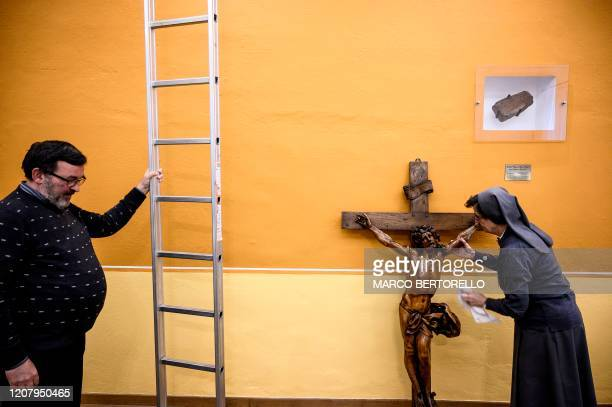 A nun cleans a wooden crucifix at the end of a streaming mass in the Chapel of the San Giovanni Bosco Oratory on March 22 2020 in Saluzzo near Cuneo...