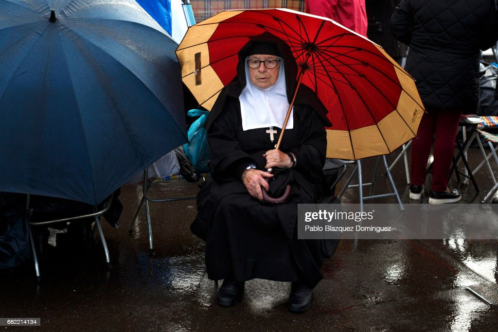 A nun covers from the rain with an umbrella as she waits for the arrival of Pope Francis in the Sanctuary of Fatima on May 12, 2017 in Fatima, Portugal. Pope Francis will be attending the Sanctuary of Fatima, in Portugal, on May 12 and 13 to canonize two Portuguese shepherds, Jacinta and Francisco Marto, who are said to have witnessed the apparition of what they believed was the Virgin Mary, together with their aunt Lucia Santos, during the 100 anniversary. Thousands of pilgrims and worshippers from around the world are expected to gather at the centenary celebration.