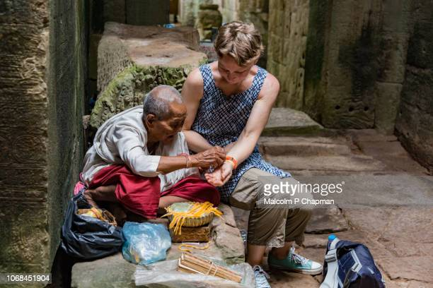 a nun gives a blessing and ties a ribbon on a tourist's wrist at preah khan temple, angkor, siem reap, cambodia - nun stock photos and pictures