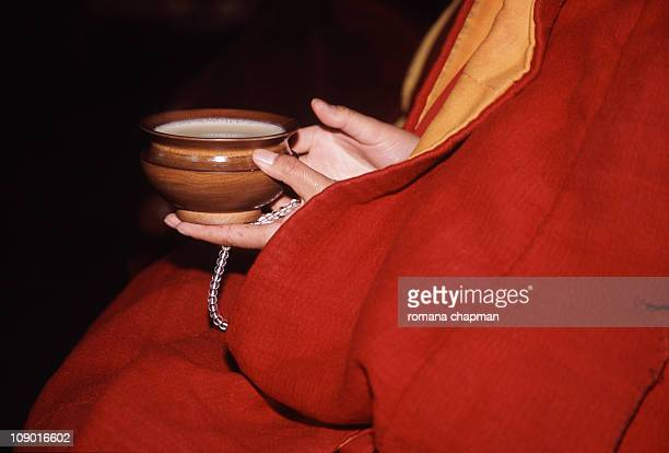 Nun holding butter tea in wooden cup