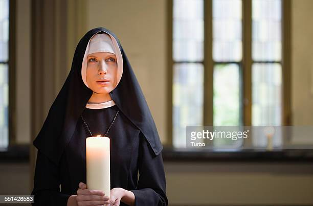 nun holding candle - nun stock photos and pictures