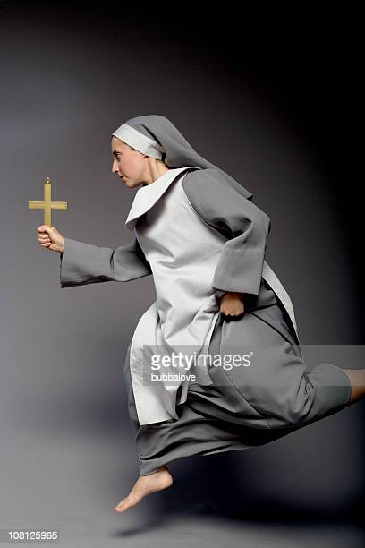 Nun Holding Cross and Running, On Gray Background