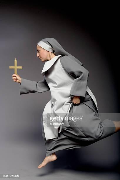 Croix religieuse tenant et, sur fond gris