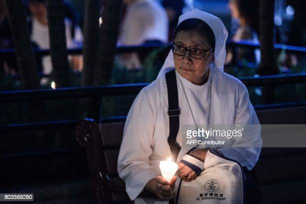 Nun holds a candle as she attends a vigil for terminally-ill Nobel laureate Liu Xiaobo in Hong Kong on June 29, 2017. Liu wants Chinese authorities...