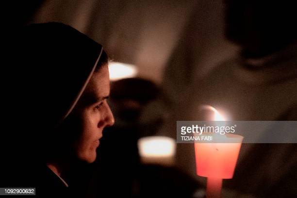 A nun holds a candle in the dark during a Pope's holy mass as part of the 23rd World Day for Consecrated Life on February 2 2019 at the Vatican