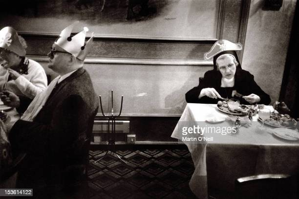 A Nun in a Christmas party hat tucks into a festive lunch as she accompanies old folk to a party in Salford Greater Manchester circa 1980
