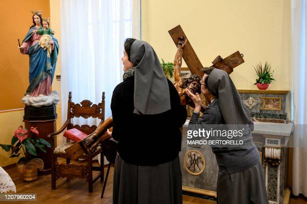 A nun kisses a wooden crucifix at the end of the streaming of Sunday mass in the Chapel of the San Giovanni Bosco Oratory on March 22 2020 in Saluzzo...