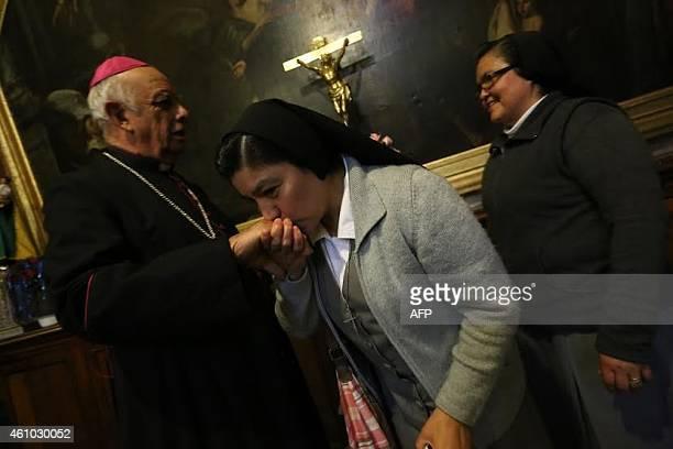 A nun kisses the hand of Mexican Archbishop of Morelia Alberto Surez Inda at Morelia Cathedral in Morelia Michoacan state Mexico on January 4 2015...
