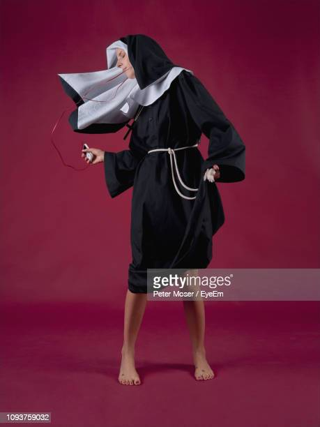 nun listening to music while dancing against red background - nun stock pictures, royalty-free photos & images