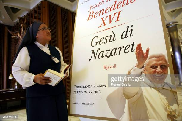 Nun looks at a banner featuring the cover of Pope Benedict XVI latest book 'Jesus of Nazareth' prior to the media conference at the Sinodo Hall on...