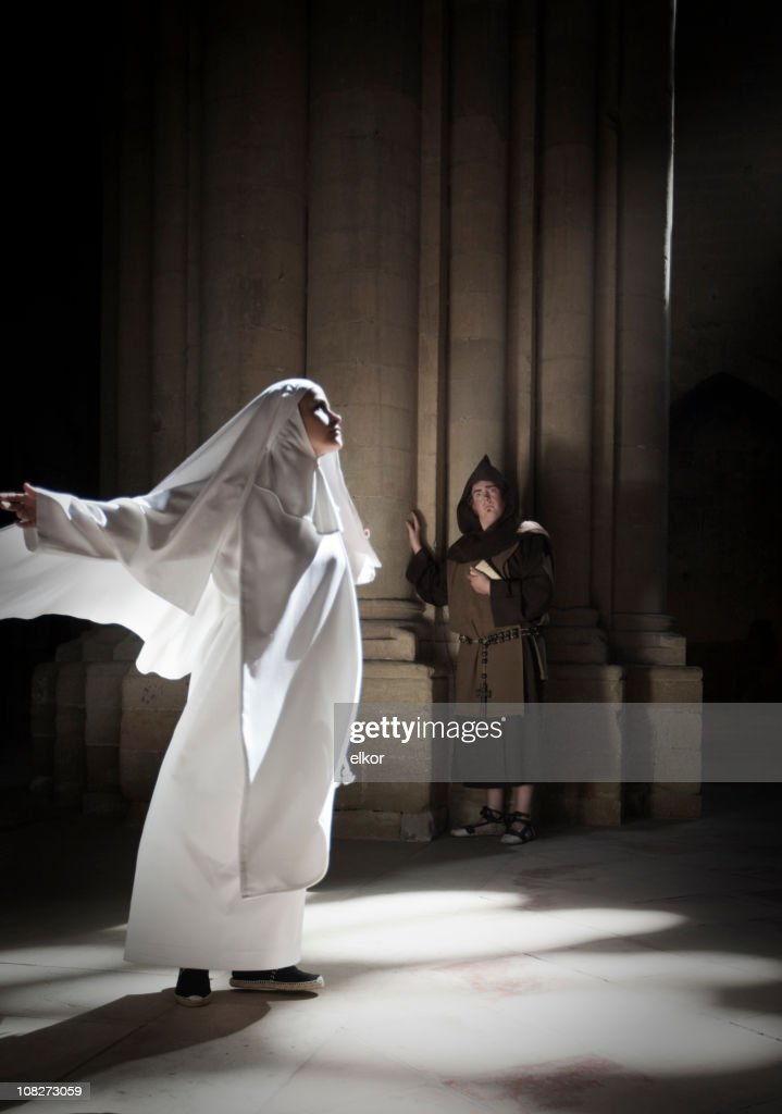 Nun meditating in sunlight from cathedral window, monk watching. : Stock Photo