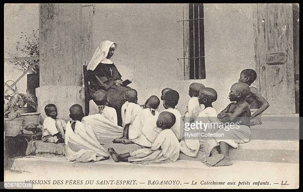 Nun of the Mission of the Fathers of SaintEsprit in Bagamayo Tanzania teaches the catechism to young African boys | Located in Rykoff Collection
