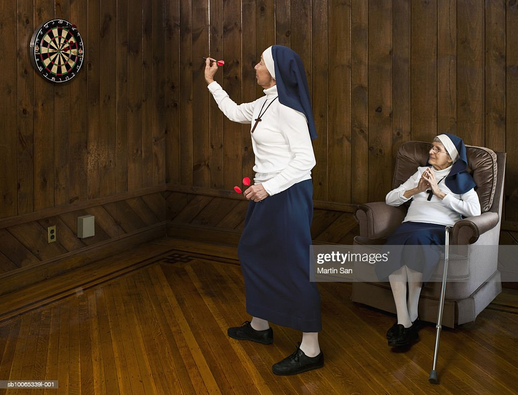 Nun playing darts and another nun watching : Foto stock