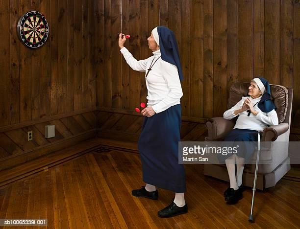 Nun playing darts and another nun watching
