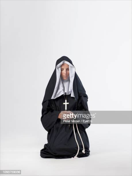 nun praying against white background - nun stock pictures, royalty-free photos & images