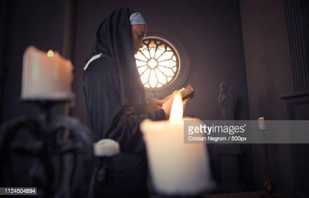 nun praying in a monastery - cristian neri foto e immagini stock