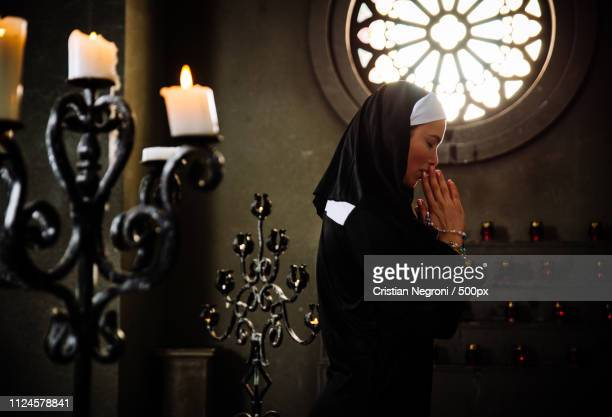 nun praying in a monastery - bonne soeur photos et images de collection