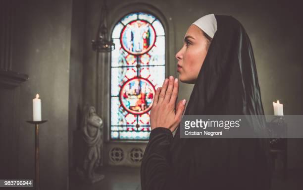 nun praying in a monastery - nun stock-fotos und bilder