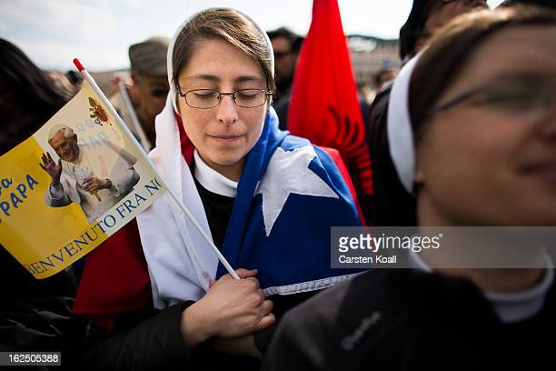 A nun prays holding a flagg pictured a photograph of Pope Benedict XVI on February 24 2013 in Vatican City Vatican Pope Benedict XVI delivers his...
