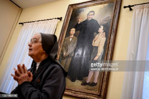 A nun prays near a paint of San Giovanni Bosco during the streaming of Sunday mass in the Chapel of the San Giovanni Bosco Oratory on March 22 2020...