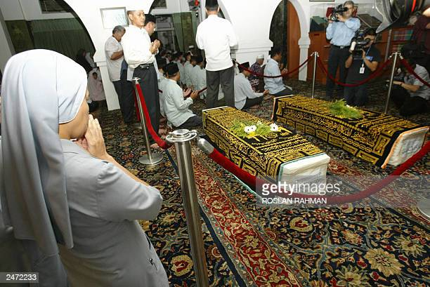 A Nun prays next to the coffins of the Iranian twins sister Laleh Bijani at the Ba'Alwi Mosque in Singapore 09 July 2003 The bodies of Ladan and...