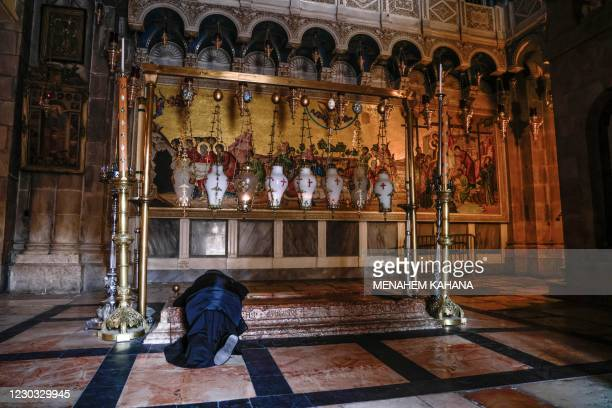Nun prays over the Unction Stone at the Church of the Holy Sepulchre, traditionally believed to be the site of Jesus' crucifixion, burial and...