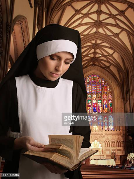 nun reading bible in the church - nun stock photos and pictures