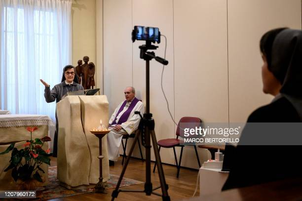 A nun reads from the Bible during the streaming of Sunday mass in the Chapel of the San Giovanni Bosco Oratory on March 22 2020 in Saluzzo near Cuneo...