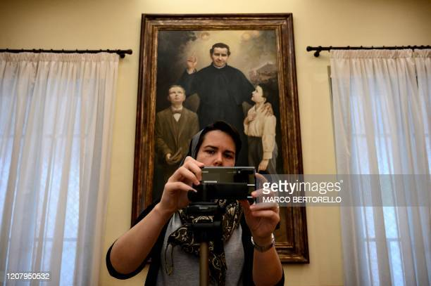 A nun sets the connection of her mobile phone used to stream Sunday mass in the Chapel of the San Giovanni Bosco Oratory on March 22 2020 in Saluzzo...